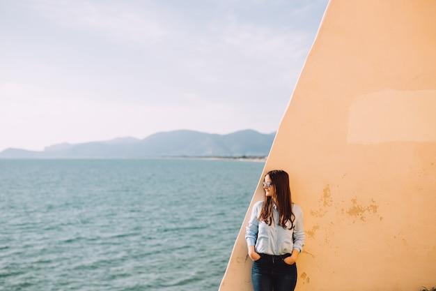 サングラスをかけた女の子が海の近くの黄色い壁に寄りかかっています。