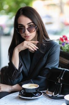 Girl with sunglasses sitting in a cafe, coffee shop, sitting on a chair in the city with red flowers, wearing sun glasses