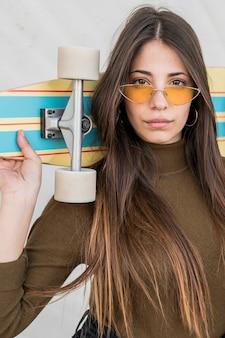 Ragazza con occhiali da sole e skateboard