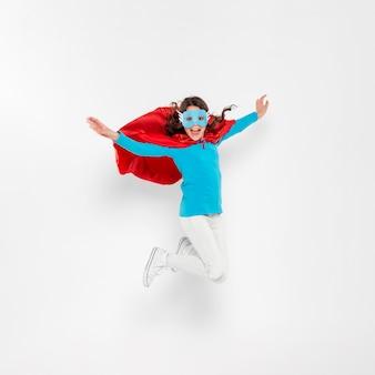 Girl with superhero costume jumping