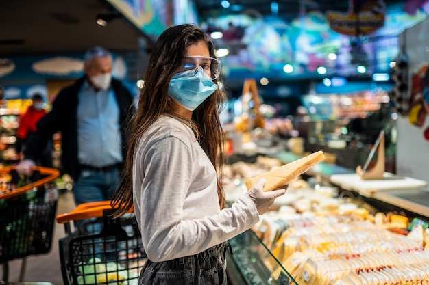 The girl with surgical mask is going to buy cheese.