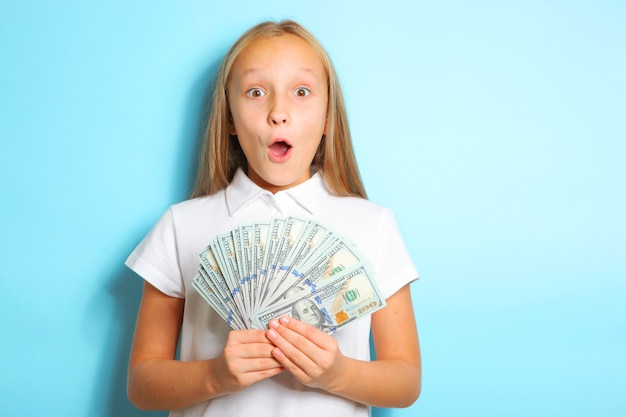 Girl with surprise emotion holding money in hands on blue background