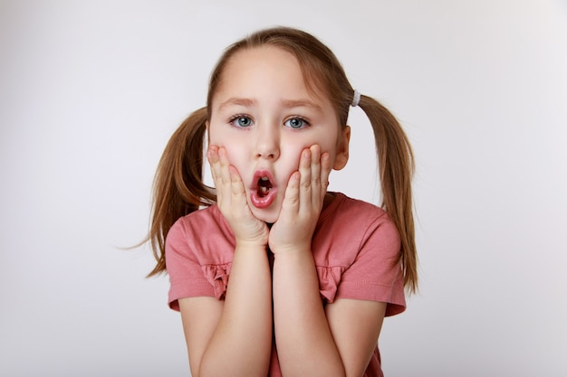 Girl with surprise suffering from toothache holding her cheek