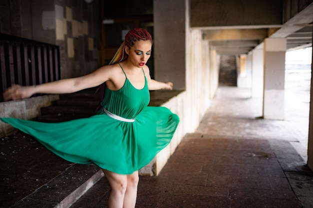 A girl with a surprised face with bright african braids and rainbow glitter makeup in a light green spring dress. jumping off the steps of a large old building in a warm spring city.