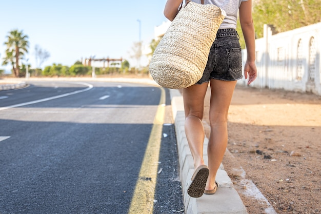 A girl with tanned legs walks along the sidewalk along the road wiht bag.