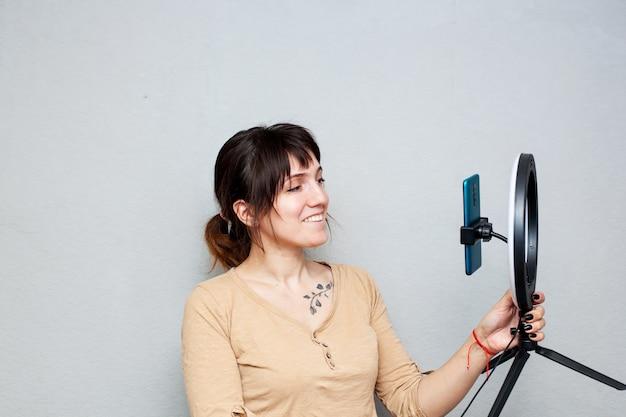鎖骨に入れ墨をした女の子がスマートフォンでビデオを録画し、灰色の壁にリングランプで自分を照らしている