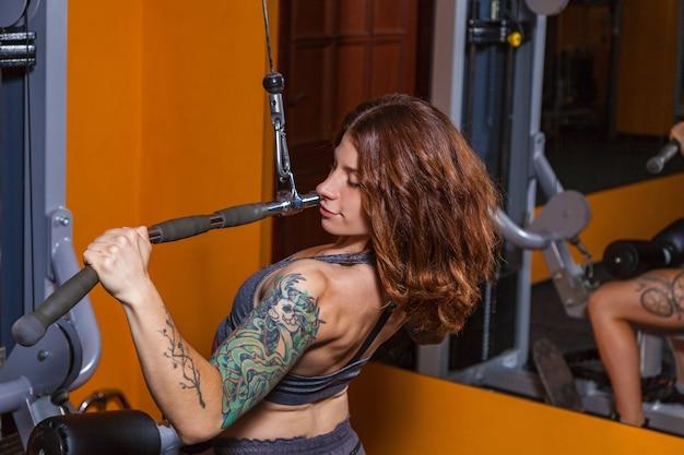 フィットネスに入れ墨をした女の子は、筋肉のある美しい体を示しています。スポーツとフィットネスのためのさまざまなスポーツ用品とフィットネス機器