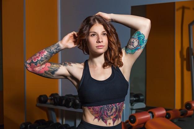 フィットネスの入れ墨を持つ少女は、筋肉のある美しい体を示しています