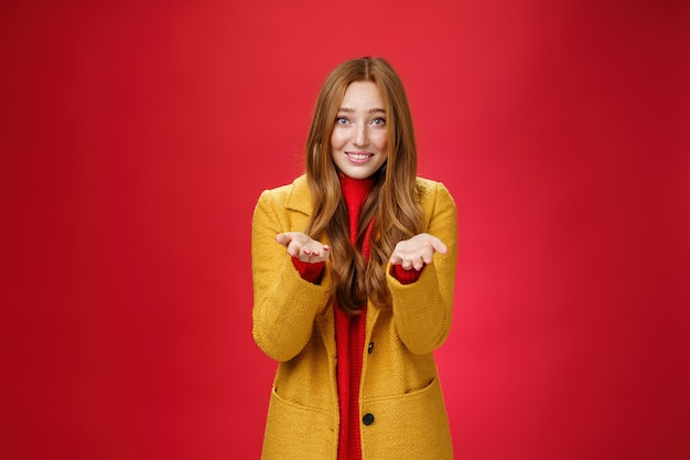 Girl with tender and caring expression smiling extanding hands forward as giving thanks or pointing at someone special feeling admiration thanking partner for support, confessing in love and sympathy.