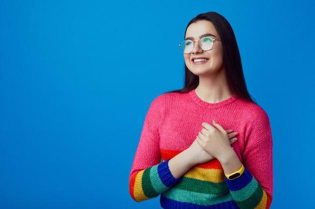 Девушка с нежной улыбкой держит обе ладони на груди в радужном свитере