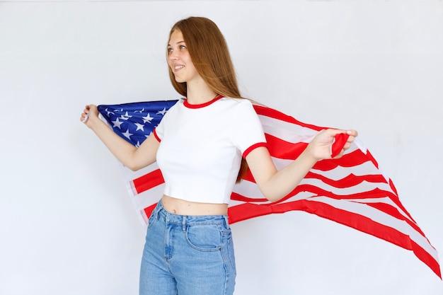 회색 배경에 미국 국기를 든 소녀