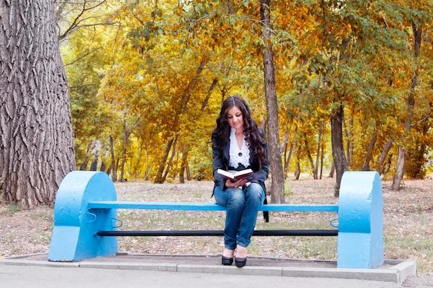 Девушка с книгой на скамейке в осеннем парке