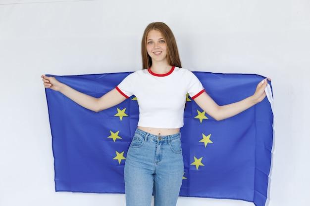 灰色の背景にeu旗を持つ少女