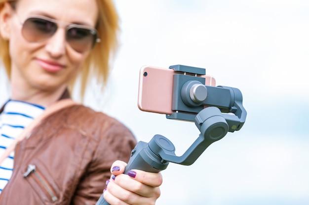 スタビライザーに携帯電話を持つ少女がビデオブログをリードしています。彼女はカメラのスマートフォンに身を任せる