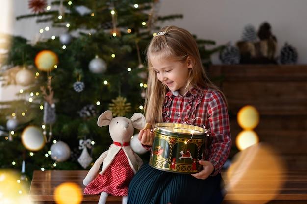 プレゼントを持った女の子がクリスマスツリーの近くに座っています