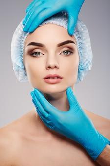 スタジオの背景に青い医療帽子をかぶった太い眉毛、患者の顔の近くに青い手袋をはめた医師の手、手術の概念、カメラを見て女の子。