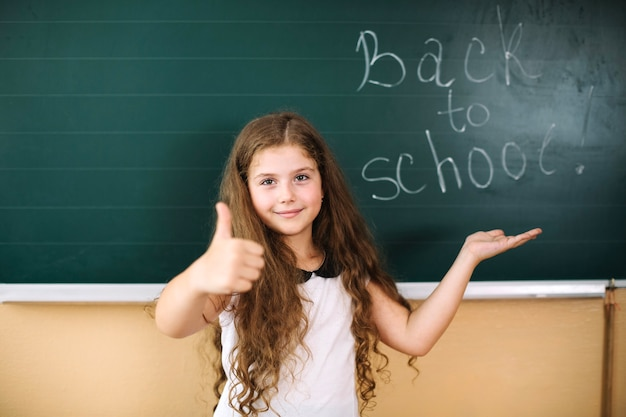 Girl with thumb up at blackboard