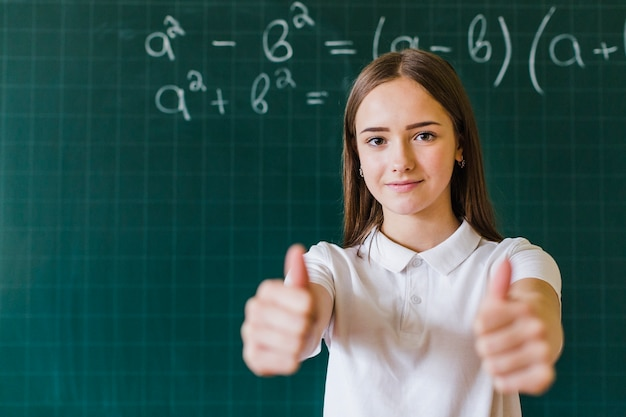 Девушка с пальцами вверх в классе математики