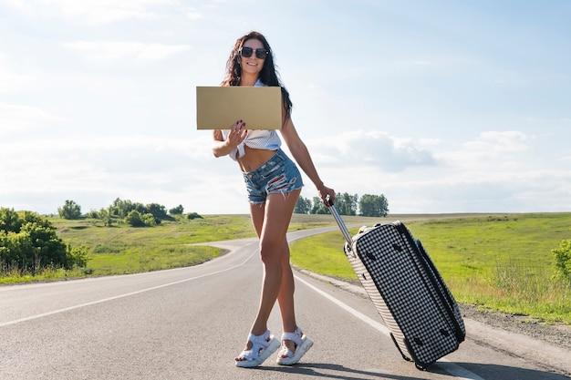 관광 가방 소녀입니다. 도로를 따라 히치하이킹을 하고 판지, 야외, 여름, 휴가, 여행 컨셉을 준비합니다. 아름다운, 젊은 섹시한 갈색 머리
