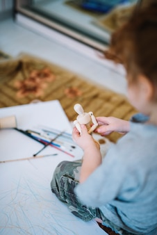 Girl with toy near papers and brushes and sitting on floor