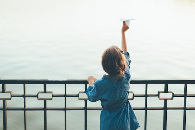Девушка с игрушкой бумажный самолетик смотрит на озеро