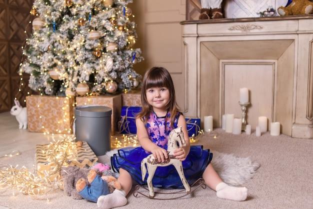 クリスマスツリーの近くのおもちゃを持つ少女