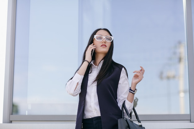 Girl with transparent glasses talking on the mobile