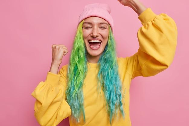 트렌디한 헤어스타일을 한 소녀는 승리를 축하하는 제스처를 통해 기쁨을 축하하며 모자를 쓰고 노란색 점퍼는 분홍색으로 격리된 코에 피어싱을 합니다