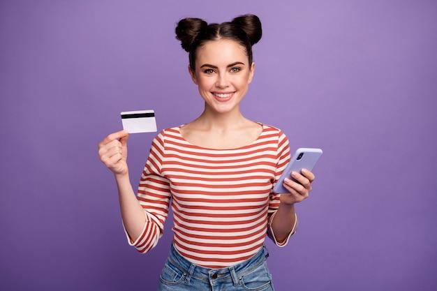 電話とクレジットカードを使用してトレンディな髪型の女の子