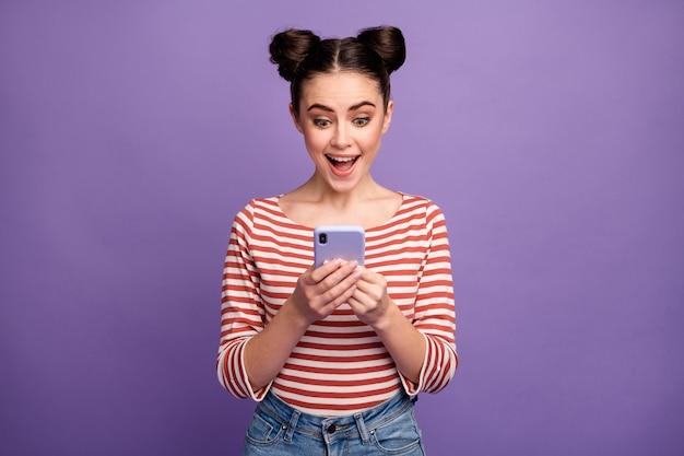 紫に分離された電話を使用してトレンディな髪型の女の子