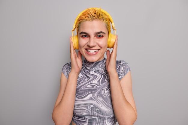 トレンディな黄色の髪型の明るいメイクの女の子は、ワイヤレスヘッドフォンで音楽を聴きます陽気な気分は灰色でカジュアルに服を着たお気に入りのロックソングを楽しんでいます