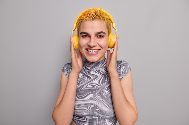 Girl with trendy yellow hairstyle bright makeup listens music in wireless headphones has cheerful mood enjoys favorite rock song dressed casually on grey