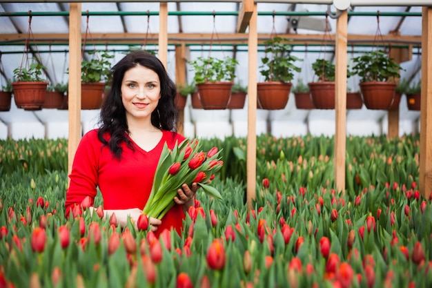 Girl with tulips grown in a greenhouse.