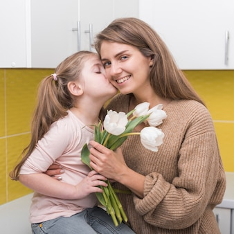 Girl with tulips kissing mother on cheek