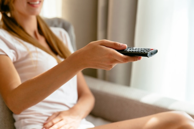 Girl with tv remote control in hand watching tv on sofa at home. close up