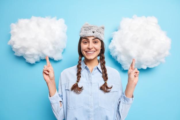 두 개의 빗질 땋은 머리를 가진 소녀는 손가락을 교차하고 행운을 빌어 희망을 품고 파란색에 머리에 셔츠 수면 마스크를 착용합니다.