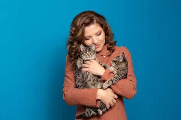 2匹のかわいいぶち子猫を持つ少女