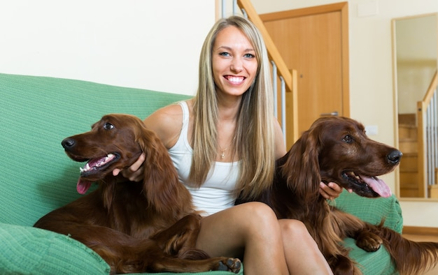 Девушка с двумя ирландскими сеттерами дома