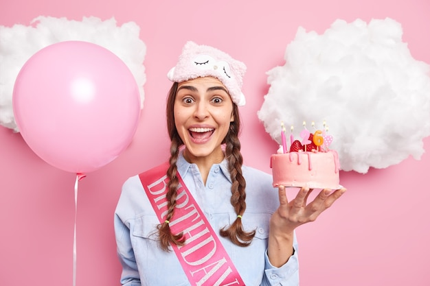 Girl with two pigtails happy to accept congratulations holds delicious strawberry cake inflated helium balloon isolated on pink