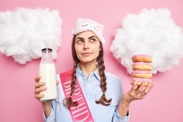 Girl with two pigtails has thoughtful expression holds pile of glazed donuts and milk bottle wears sleepmask and shirt isolated on pink