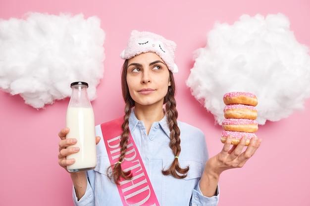 Девушка с двумя косичками с задумчивым выражением лица держит кучу глазированных пончиков, а бутылка молока носит маску для сна и рубашку, изолированную на розовом