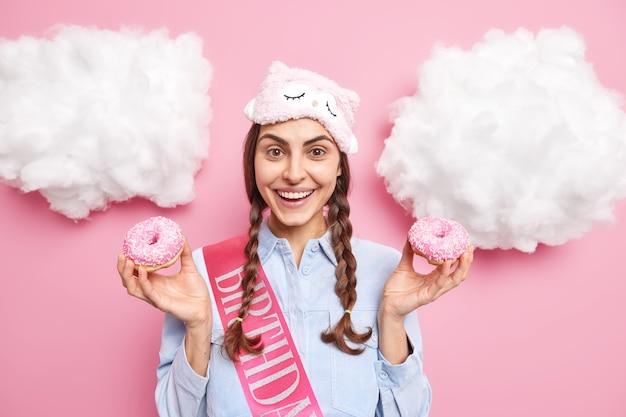 2 つのおさげの笑顔を持つ少女は、友人の誕生日を積極的に祝うピンクに隔離されたカジュアルな家庭服を着た 2 つのおいしい釉ドーナツを保持します。