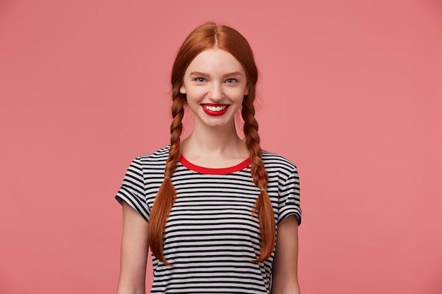 2つの赤い髪の三つ編み、魅力的な歯を見せる笑顔、剥ぎ取られたtシャツに身を包んだ赤い口紅を使用した女の子、孤立