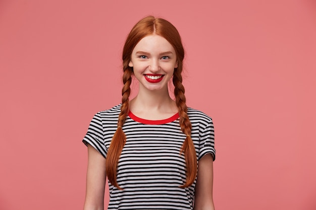 Girl with two red haired braids, charming toothy smile, used red lipstick dressed in stripped t-shirt, isolated