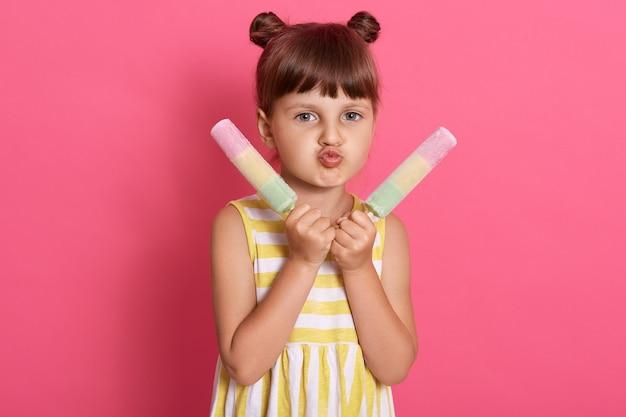 カメラを見て、顔をしかめる、ふくれっ面の唇を作る2つのウォーターアイスクリームを持つ少女は、ピンクの背景に分離された立っている縞模様の夏のドレスを着ています。