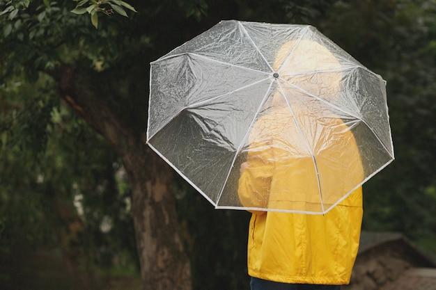 緑の背景に雨の傘を持つ少女