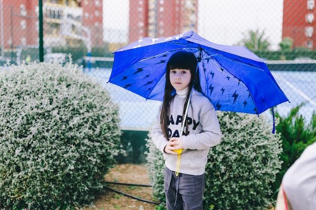 Girl with umbrella near bushes