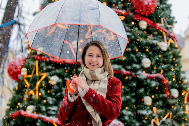Girl with umbrella near christmas tree