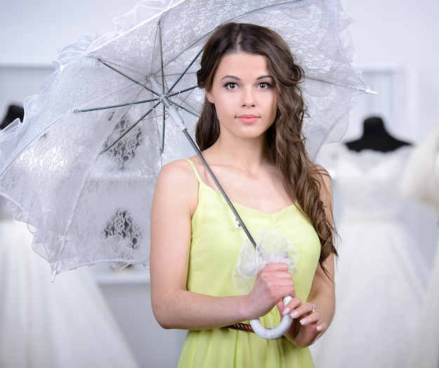 Girl with an umbrella in a wedding dress store.