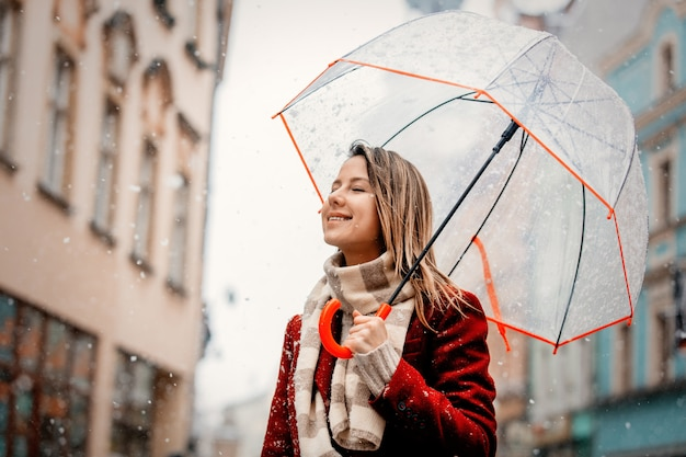 Girl with umbrella white snow falling stay on city street